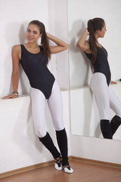 Fitness woman in leotard and white leggings