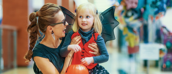 smiling elegant mother and daughter on Halloween at mall