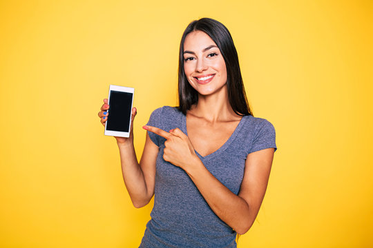 Choice it! Technology, mobile, equipment for communication. Young beautiful woman shows right in camera the blank screen of smart phone on yellow background