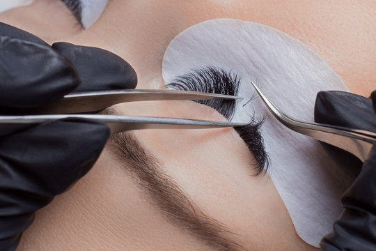 Eyelash extension procedure. Woman master making long lash