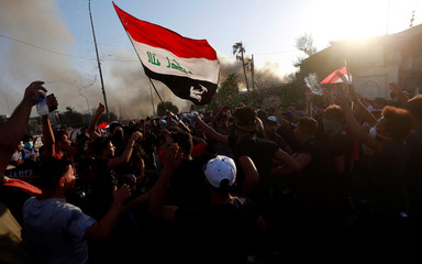 People gather during a protest near the building of the government office in Basra