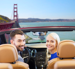 road trip, travel and people concept - happy couple driving in convertible car and looking back over golden gate bridge in san francisco bay background