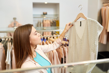shopping, fashion, sale and people concept - young woman choosing shirt in mall or clothing store