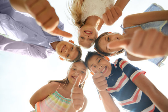 childhood, friendship and gesture concept - group of smiling happy children showing thumbs up in circle