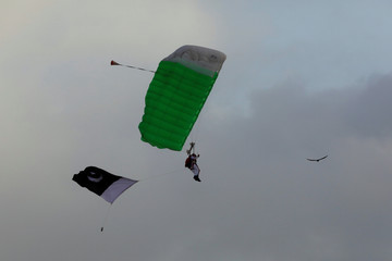 A member of Pakistan Navy special force parachutes with a national flag, during Defence Day ceremonies, or Pakistan's Memorial Day, in Karachi