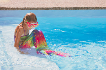 Young Caucasian girl with mermaid costume in swimming pool