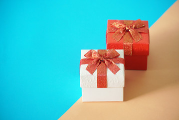 Red and white gift boxes on blur and brown background, picture have space for idea.