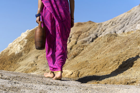 a barefooted woman in ethnical clothes carries in her hand a clay jug