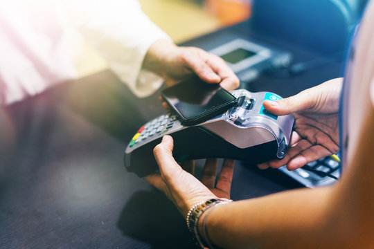 woman use smartphone to make mobile payment with electronic reader. customer paying with near field communication, NFC technology. people use app in mobile phone for online shopping.