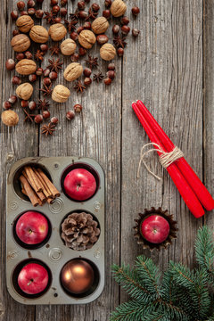 Christmas  background with fir tree branches, red apples, walnuts, hazelnut, nutcracker, cinnamon and red candles.