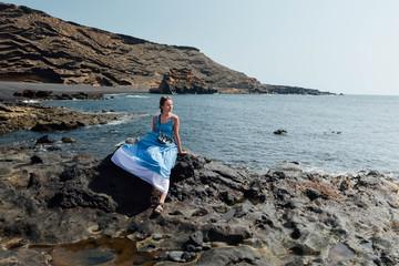 Beautiful girl sitting on rock beach