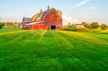 Setting Sun Casts Shadows on an Old Red Barn in Minnesota Wall mural