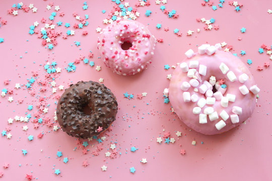 Colorful donuts in the glaze on the pink background with multi-colored sprinkles sugar stars. Can be used as a background for birthday or other holidayn