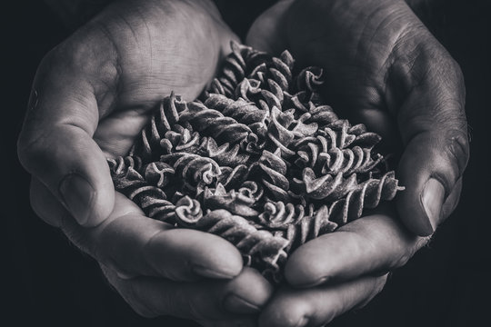 Rough rough masculine hands hold Italian pasta - black and white