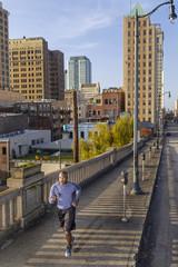 Man jogging along bridge in city, Birmingham, Alabama, USA