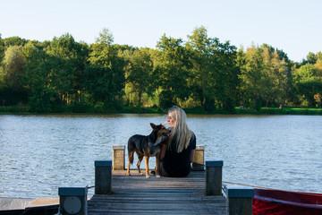 Junges Mädchen und ihr Hund gemeinsam auf einen Bootssteg. Die junge Frau lächelt natürlich zu ihrem Hund. Standort: Deutschland, Nordrhein Westfalen