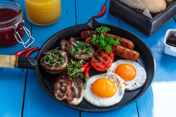 Close view English Breakfast in a pan with fried eggs, sausages, bacon, mushrooms, jam and orange juice on wooden background