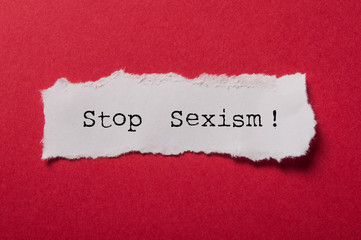 closeup of white torn paper on red paper background - Stop Sexism !