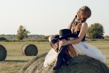 Sexy woman with cowboy hat and dress at haystack resting after work