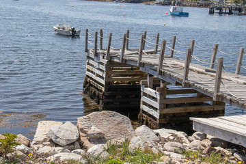 Wooden pier supports with rocks in foreground and boats water in background, summer, no people.
