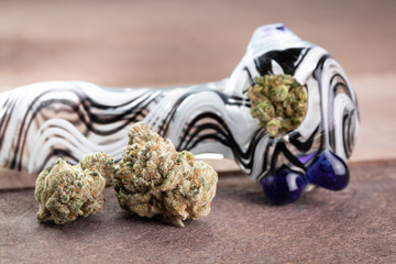 Marijuana buds on wood, beside a packed marijuana pipe