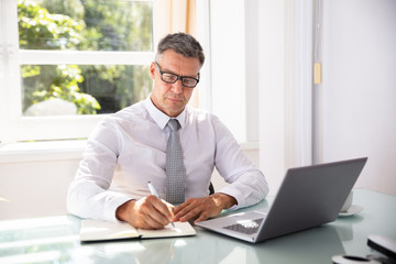 Businessman Writing Schedule In Diary With Pen