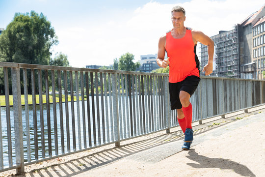 Mature Athletic Man Running On Sidewalk