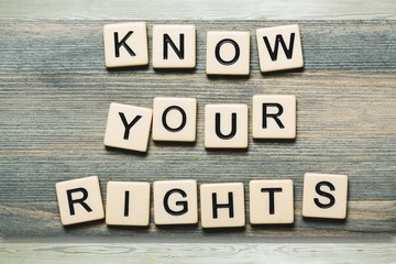 Know Your Rights sign with wooden cubes on background