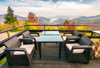 terrace with beautiful view in to the mountains. autumn season with red foliage on forested hills. cloud inversion in distant valley. wonderful vacation concept