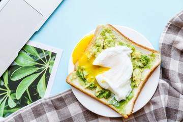 Healthy Breakfast with Bread Toast and Poached Egg with Green Avocado. Flat lay desktop with laptop