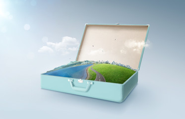 City skyline, green field, lake, mountain and curvy asphalt highway  in an open retro vintage suitcase isolated on light blue background .