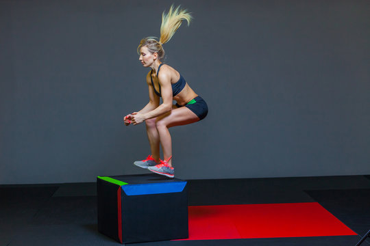 Beautiful female fitness athlete performs box jumps in a dark gym wearing black sports top and short tights with face hidden.