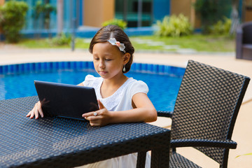 A beautiful, elegant girl of 8 years sitting with a laptop and books outdoors, studying at an...