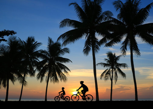 silhouette Father and son riding bicycle at sunset sky