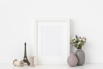 Elegant white a5 portrait frame mockup with dried field wild flowers in vases, Eiffel Tower and silk ribbons on and white wall background. Empty frame, poster mock up for presentation design.