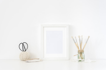 White frame mockup A5 in interior. Frame mock up background for poster or photo frame for bloggers, social media, lettering, art and design. Indoor, frame on table. Summer sea mood
