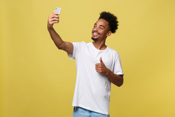 young afro american black man smiling happy taking selfie self portrait picture with mobile phone looking excited having fun posing cool isolated in yellow background in communication technology
