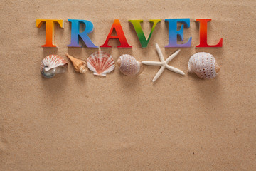 top view of travel written in colorful letters decorate with shellfish on the beach with copy space