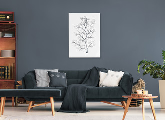 Wooden table and bench in front of sofa with pillows in dark flat interior with poster and plant. Real photo
