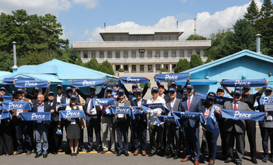 South Korean Culture, Sports and Tourism Minister Do Jong-whan, center, and members of the diplomatic corps in South Korea hold their banners for a photograph at the border village of Panmunjom in the Demilitarized Zone