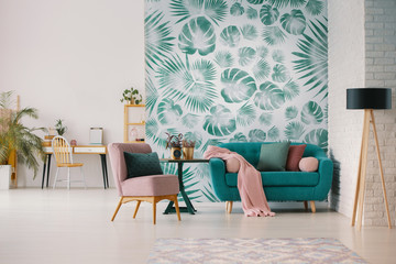 Pink armchair and blue settee in living room interior with green wallpaper and lamp. Real photo