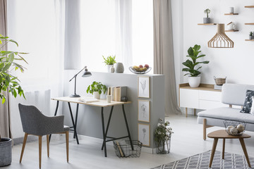 Real photo of a bright home office interior with a desk, armchair and plants