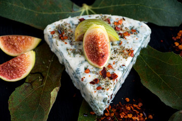 Ein Stück Gorgonzola mit Feigen und Paprikapulver auf einem Feigenblatt