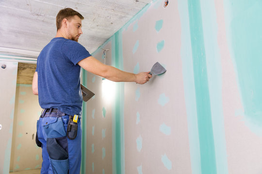 apartment interior construction - worker plastering gypsum board wall