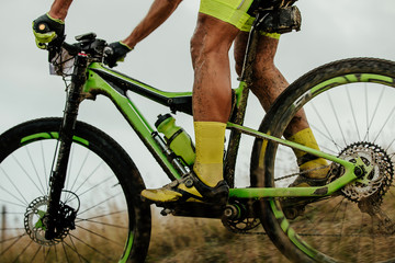 dirty feet athlete cyclist rides on mountainbike with water bottle