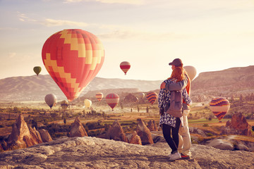 Wall Mural - Couple travelers watching the hot air balloons at the hill