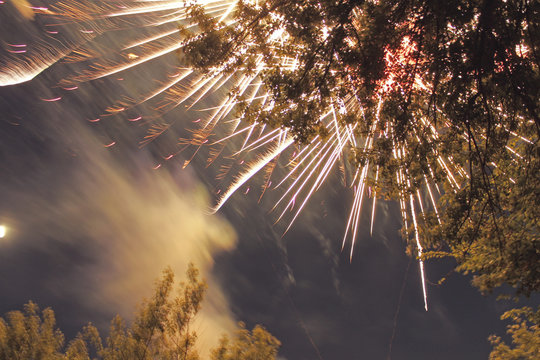 yellow fireworks sparks through the leaves of the tree