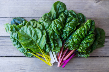 Organic rainbow chard: spray-free leafy greens in fan arrangement on rustic wooden background