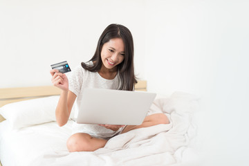 Woman pay on credit card with laptop computer on bed
