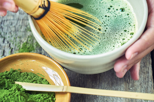 Matcha green tea accessoires on the rough wooden boards with girl's hands preparing matcha tea in a clay bowl